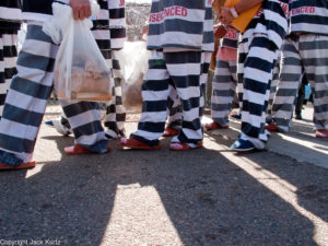 """04 FEBRUARY 2009 -- Undocumented immigrant prisoners walk into tent city. Maricopa County Sheriff Joe Arpaio marched about 200 undocumented immigrants in the Durango Jail to """"Tent City"""" where he will house the prisoners until or if they are deported. PHOTO BY JACK KURTZ"""